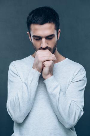 hombre orando: Mendigando por ... Tiro del estudio del hombre joven y guapo rezando mientras mantiene las manos juntas y mantener los ojos cerrados