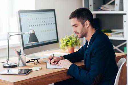 hombre escribiendo: Concentrado en el trabajo. Vista lateral del hombre joven confidente escribiendo algo en su cuaderno mientras estaba sentado en su puesto de trabajo en la oficina