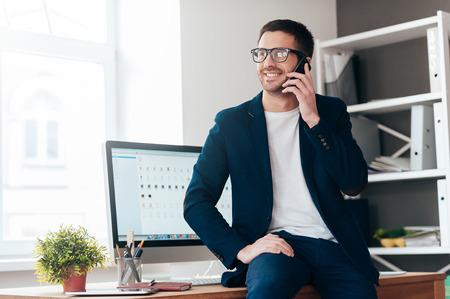큰 거래에 대한 좋은 하루. 잘 생긴 젊은 남자 사무실에서 책상에 기대어 동안 휴대 전화에 얘기 하 고 웃 스톡 콘텐츠 - 49292902