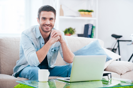 idea comfortable: Enjoying time at home. Handsome young man looking at camera and smiling while sitting on the couch at home with laptop laying near him
