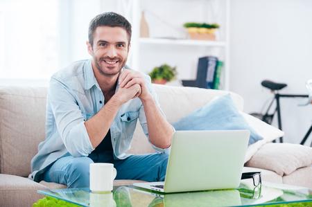Tempo desfrutando em casa. Homem novo considerável olhando para câmera e sorrindo, sentado no sofá em casa com o portátil que coloca perto dele