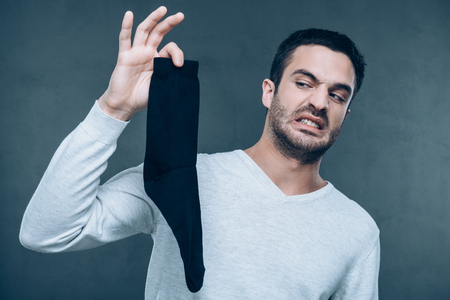 unpleasant smell: What is that?! Frustrated young man expressing negativity and covering nose with fingers while holding black sock and standing against grey background Stock Photo