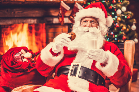 traditional gifts: My favorite meal! Cheerful Santa Claus holding glass with milk and cookie while sitting at his chair with fireplace and Christmas Tree in the background