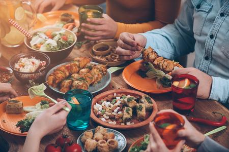 フレンドリーなディナー。素朴な木製のテーブルに座っている間に一緒にディナーを持つ人々 のグループのトップ ビュー 写真素材