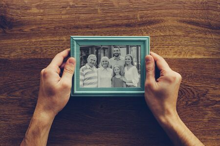I love my family! Close-up top view of man holding photograph of his family over wooden desk photo
