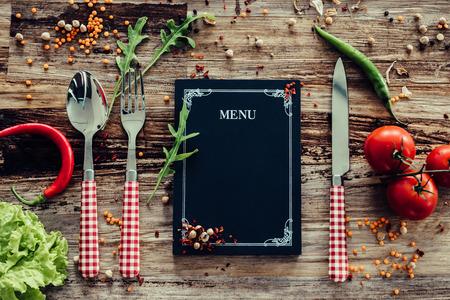 レストランのメニュー。周囲に野菜と素朴な木の机の上に敷設、黒板メニューのトップ ビュー 写真素材