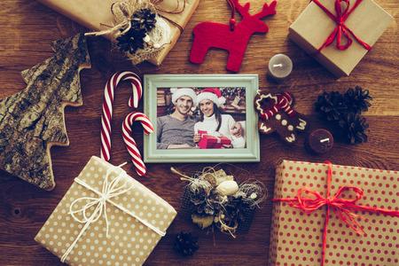 Memórias brilhantes. Vista de cima de decorações de Natal e fotografia no frame de retrato que coloca no grão de madeira rústica