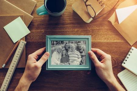 Meine Familie ist meine Inspiration. Close-up Draufsicht Mann mit Foto von seiner Familie über Schreibtisch aus Holz mit verschiedenen Kanzlei Zeug herumliegen