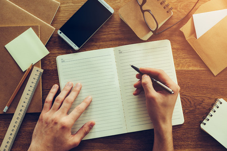 creativity: Just inspired. Close-up top view of man writing something in notebook while sitting at the wooden desk with different chancellery stuff laying around Stock Photo