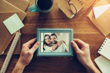 business relationship: Bright moments together. Close-up top view of man holding photograph of young couple over wooden desk with different chancellery stuff laying around Stock Photo