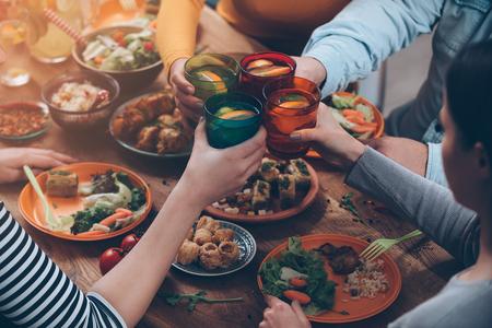 saúde: Cheers para nós! Vista de cima de pessoas torcendo com bebidas enquanto está sentado à mesa de jantar rústica