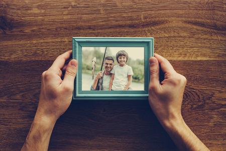 Mon fils est ma vie. Close-up vue de dessus de l'homme tenant la photo de lui-même et son fils de pêche au cours bureau en bois