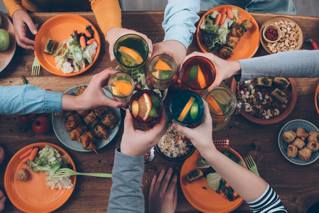 Cheers! Top view of people cheering with drinks while sitting at the rustic dining table 스톡 콘텐츠