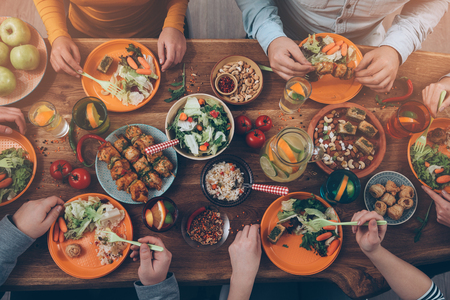 食べ物: 友人とディナーを楽しんでいます。素朴な木製のテーブルに座っている間に一緒にディナーを持つ人々 のグループのトップ ビュー