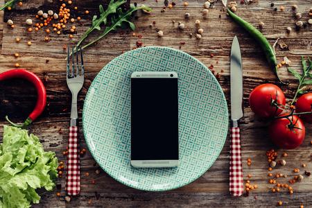 Bel voor levering. Bovenaanzicht van de plaat en de slimme telefoon tot op de rustieke houten bureau met groenten rond