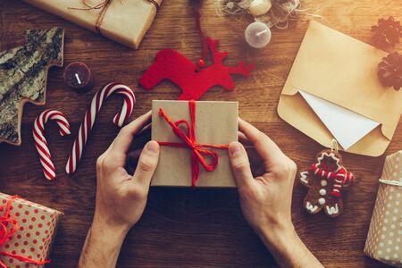 Abrindo presente de Natal. Close-up vista superior do homem abrindo a caixa de presente na mesa de madeira com as decorações de Natal, que volta