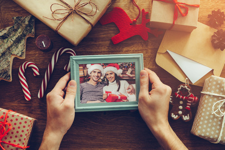 christmas gift box: Christmas mood. Top view of Christmas decorations and photograph in picture frame laying on the rustic wooden grain