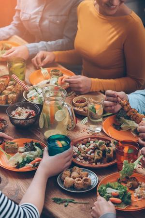 Dinning juntos. Vista de cima de um grupo de pessoas tendo jantar juntos enquanto está sentado na mesa de madeira rústica Imagens