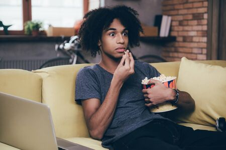 african man: Horror movie. Young African man watching TV and looking scared while eating popcorn sitting on the couch at home