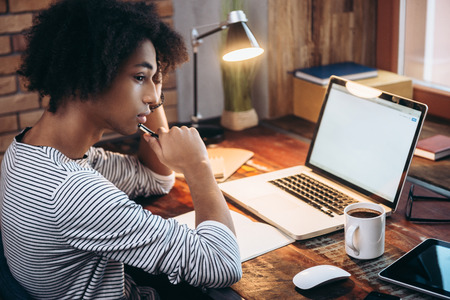 motivation: Searching for inspiration. Side view of young African man holding hand on chin and looking away while sitting at his working place