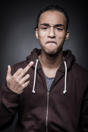 rudeness: Get off me! Portrait of furious young African man looking at camera and gesturing while standing against black background Stock Photo