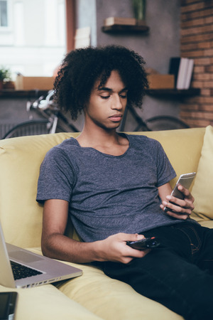young men: Another message. Young African man holding remote control and looking at his smart phone while watching TV on the couch at home