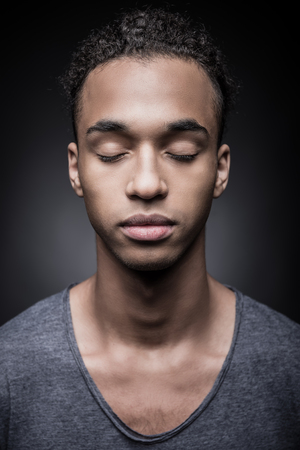 Calm and confident. Portrait of young African man keeping eyes closed while standing against black background