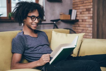 persona leyendo: Disfrutando nuevo capítulo. Vista lateral de la joven alegre libro de lectura del hombre africano con sonrisa y con gafas mientras estaba sentado en el sofá de casa