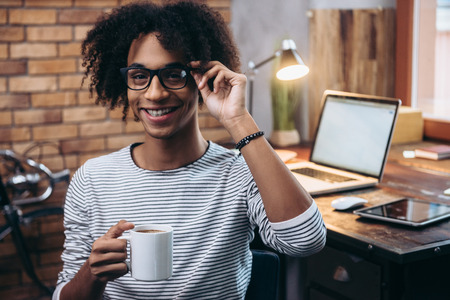 resting: Coffee break. Cheerful young African man holding coffee cup and adjusting his glasses with smile while sitting beside his working place