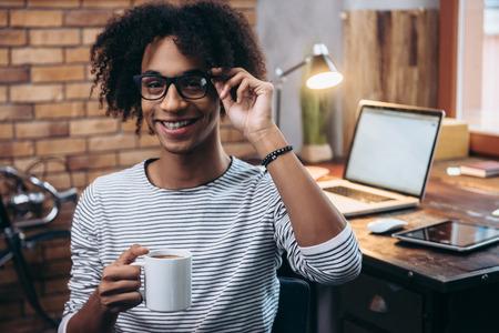 empleado de oficina: Pausa para el caf�. Hombre africano joven alegre que sostiene la taza de caf� y ajustando sus gafas con una sonrisa mientras se est� sentado al lado de su lugar de trabajo