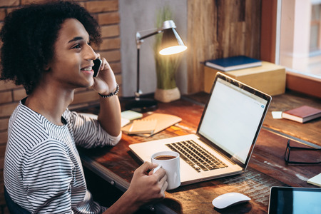 work from home: Discussing new ideas. Side view of cheerful young African man talking on mobile phone and holding coffee cup while sitting at his working place Stock Photo