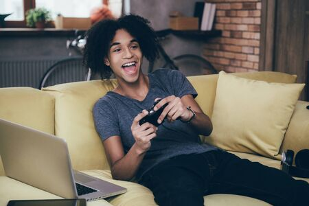 Games always fun. Cheerful young African man playing video game and keeping his mouth open while sitting on the couch at home Imagens