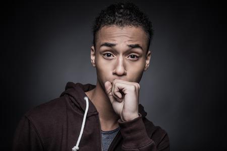 tosiendo: ¡Venga! Retrato de hombre joven africano que mira la cámara y que cubre su boca con el puño mientras está de pie contra el fondo negro