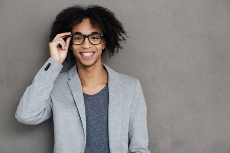 adjusting: I clearly see you! Cheerful young African man looking at camera with smile and adjusting his glasseswhile standing against grey background Stock Photo