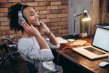 His favorite song. Side view of cheerful young African man adjusting headphones and keeping eyes closed while sitting at his working place Standard-Bild
