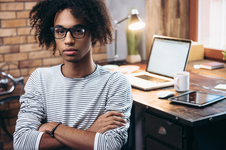 man studying: Young and confident. Handsome young African man crossing his arms and looking at camera while sitting besidehis working place Stock Photo