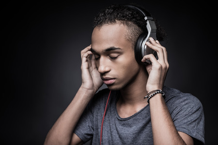 Soul music. Side view of young African man adjusting headphones and keeping eyes closed while standing against black background