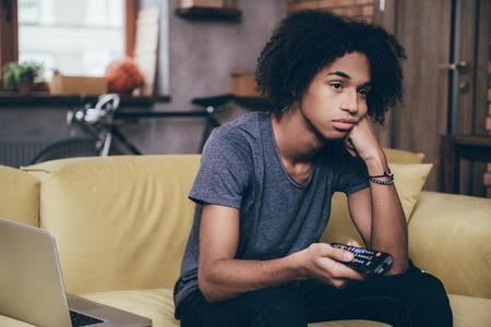 viendo television: Nada interesante de ver. Hombre africano joven que sostiene el control remoto y con aspecto aburrido mientras ve la televisión en el sofá en casa Foto de archivo