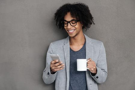 hombres jovenes: Siempre en contacto. El hombre africano joven alegre que sostiene el teléfono elegante y mirándolo con una sonrisa mientras está de pie contra el fondo gris con la taza de café