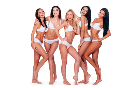 Natural beauty. Full length of five beautiful young women in lingerie posing and smiling while bonding to each other and standing against white background Banco de Imagens