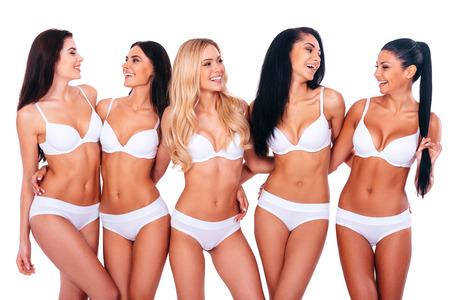 Bellezas sin preocupaciones. Grupo de mujeres alegres en la ropa interior que abraza y mirando el uno al otro mientras está de pie contra el fondo blanco Foto de archivo