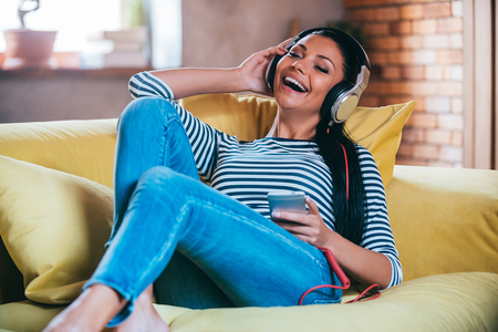 women legs: Enjoying music at home. Happy young woman adjusting her headphones and keeping eyes closed while lying on the couch at home