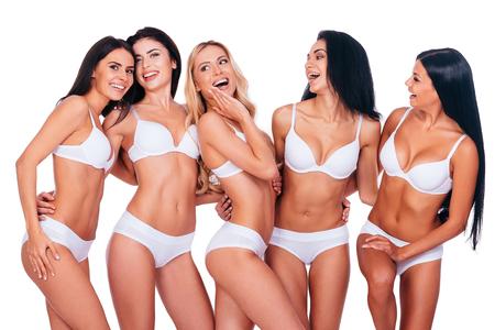 Beautés parfaites. Cinq belles femmes posant en lingerie et en regardant naturel tout debout ensemble sur le fond blanc