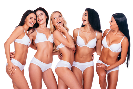 sex symbol: Perfect beauties. Five beautiful women in lingerie posing and looking natural while standing together against white background