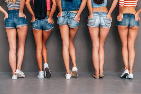 Mains dans les poches. Close-up vue arrière de cinq femmes portant des shorts jeans et se tenant la main dans leurs poches tout en se tenant sur fond gris