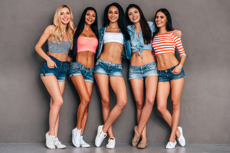 Young and carefree. Full length of five beautiful young women bonding and smiling while standing against grey background