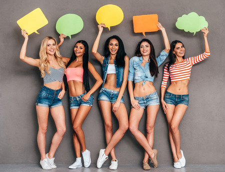 group shot: Got some ideas? Full length of five beautiful young women holding speech bubbles with copy space over their head while standing together against grey background
