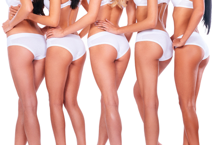 beautiful nude women: Bootylicious. Close-up rear view of five women wearing white panties and showing their perfect legs and buttocks while standing against white background