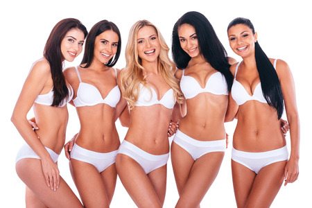sex pose: Confident in their perfect bodies. Group of five beautiful women in lingerie bonding to each other and smiling while posing against white background Stock Photo