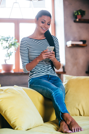 women legs: Enjoying her new mobile phone. Beautiful young woman holding smart phone and looking at it with smile while sitting on the couch at home